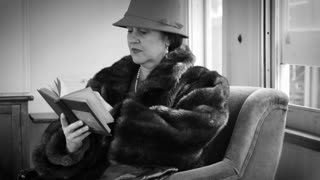 thirties woman reading a book while on a train 4k