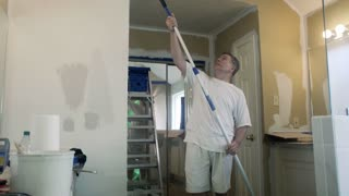tilt to man painting the ceiling of a bathroom 4k