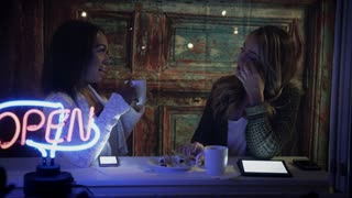 two young women laughing and talking in a coffee shop 4k