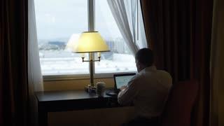 wide shot businessman working in a dark hotel room at the window 4k