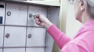 woman going to a community keyed mailbox for her mail 4k