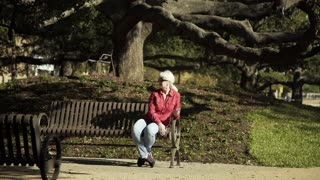 Woman In A Public Park Sitting On A Bench Looking Around 4 K