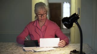 woman in her kitchen paying bills and worried 4k