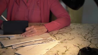 woman sitting at a table going over bills 4k
