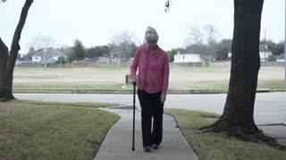 woman walking with a cane on a suburban sidewalk 4k