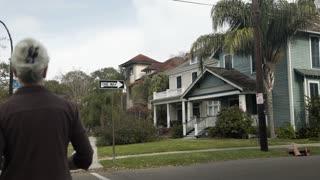 woman walks past camera in establishing shot of new orleans homes 4k