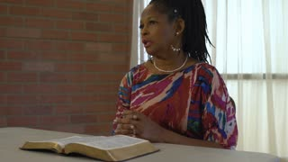 Woman with Bible on table in front of her talks to those off scene