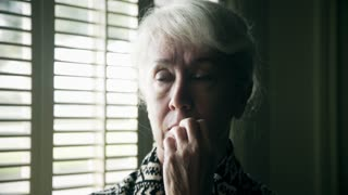 worried confused looking older woman at a window 4k