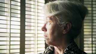 worried woman standing next to a window 4k