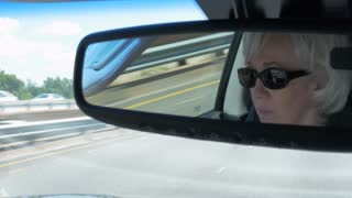 View from the rearview mirror of a mature woman driving on an interstate highway 4k