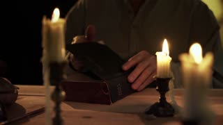 vintage 1800s man reading bible by candlelight 4k