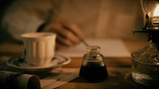 vintage man writing with a dip ink pen by oil lamp 4k