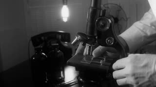vintage scientist using a microscope.