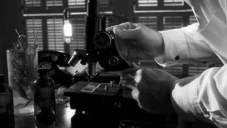 vintage scientist working with a microscope BW 4k