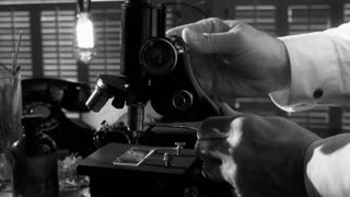vintage scientist working with a microscope BW