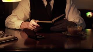 vintage thirties closeup man pours milk in coffee reads book 4k