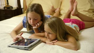 wide shot little girls playing games on a tablet pc