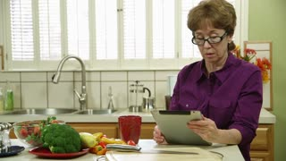 wide shot mature woman using a tablet pc