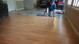 wide shot of workman removing laminate flooring