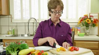wide shot woman cutting peppers.