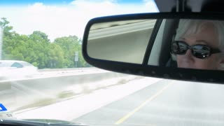 wider view from rear view mirror of woman driving on an interstate highway