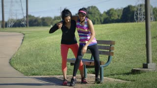 woman helping her exercise partner get help from a leg injury