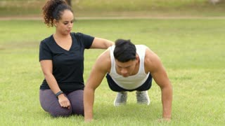 woman helping her male friend do pushups in a park