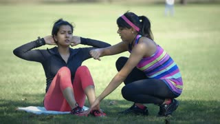 woman helping time her friend perform situps in a park