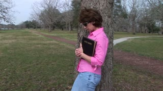 woman holding her bible in a park
