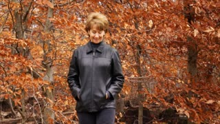 woman in autumn forest walks past camera