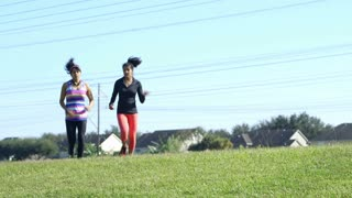 woman jogging with her friend slips and sprains her ankle