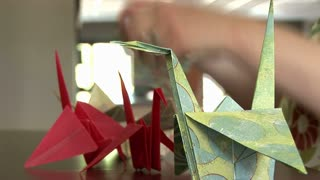 woman placing origami on a table