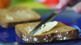 woman putting butter on two slices of toast 4k