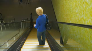 woman riding down an escalator 4k