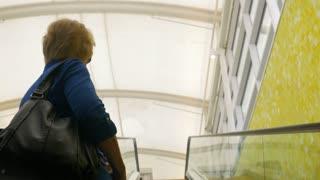 woman riding up an escalator
