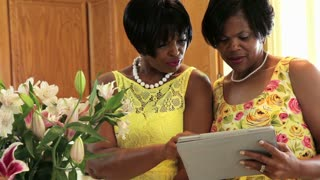 woman showing friend tablet pc and smile at camera.