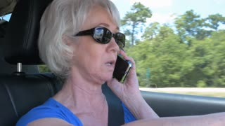 woman talking on a cell phone while driving on an interstate highway 4k