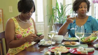 woman texting during lunch with her friends