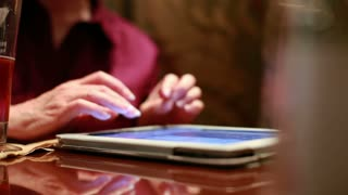 woman using a tablet pc in a restaurant.