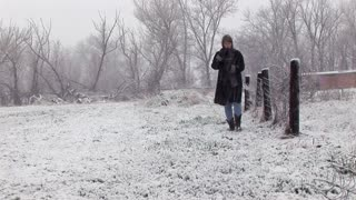 woman walking in the snow holding a bible