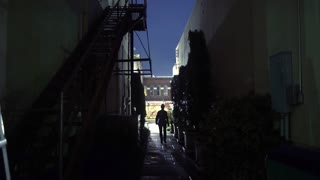 woman walks toward camera from dark alley 4k