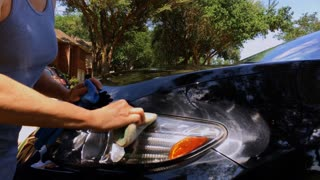 woman waxing the car on a sunny day 4k