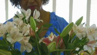 woman with flower arrangement smiles at camera.