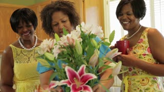 women arranging flowers and smile at camera.