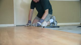worker removing laminate flooring