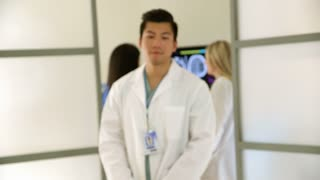 young Asian medical intern looks unsmiling into camera