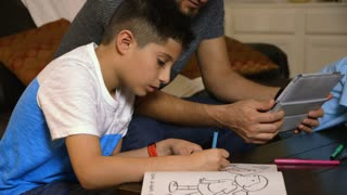 Young boy drawing while his dad watches