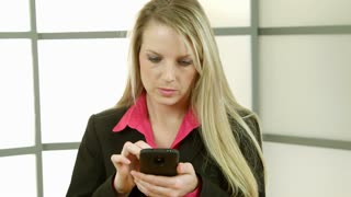 young businesswoman texting smiles at camera