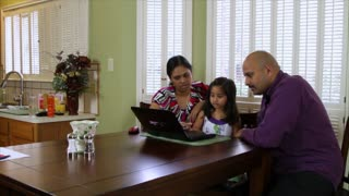 Young family using a laptop in the kitchen