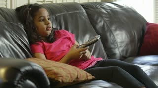 Young girl sitting on sofa changing TV channels using remote controller
